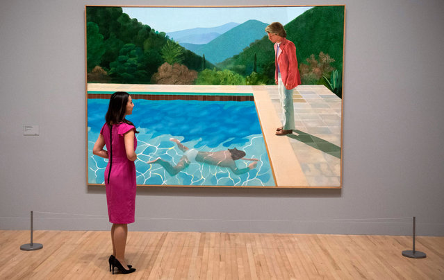 """A member of gallery staff looks at a painting called """"Portrait of an Artist (Pool with Two Figures)"""" British artist David Hockney during a press preview of a retrospective of his work at Tate Britain, Central London, Britain, 06 February 2017. (Photo by Will Oliver/EPA)"""