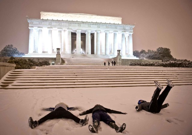 """Young people make """"snow angel"""" shapes in the snow in front of the Lincoln Memorial as a heavy snow storm hits Washington D.C. on February 13, 2014. The eastern US, in the grips of one of the most brutal winters in recent memory, braced for what forecasters warned could be the worst broadside yet – a massive storm with the season's heaviest snowfall. (Photo by /AFP Photo)"""