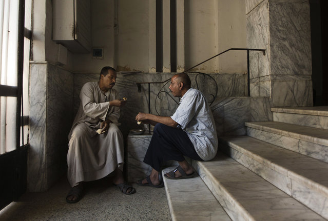 In this Tuesday, April 28, 2015 photo,  Salama Osman, left, eats breakfast with Hagag Mohammed, a fellow doorman in his neighborhood, in the foyer to the apartment building where he works in Cairo, Egypt. Osman speaks every day by phone to his wife and children back in southern village of Abu Al-Nasr, but the money he makes in Cairo can support his wife, Amira, and his four children, forcing him to continue his migrant life in the big city. (Photo by Hiro Komae/AP Photo)