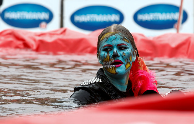 """A woman takes part in the comic competition """"Californication 9.0"""" as she jumps into the ice water to mark the end of winter at an entertainment centre near the town of Logoisk, Belarus April 7, 2019. (Photo by Vasily Fedosenko/Reuters)"""