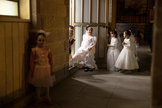 Ultra-Orthodox Jewish children play before reading the book of Esther at a synagogue in the Israeli city of Beit Shemesh on March 23, 2016 during the feast of Purim. The carnival-like Purim holiday is celebrated with parades and costume parties to commemorate the deliverance of the Jewish people from a plot to exterminate them in the ancient Persian empire 2,500 years ago, as recorded in the Biblical Book of Esther. (Photo by Menahem Kahana/AFP Photo)