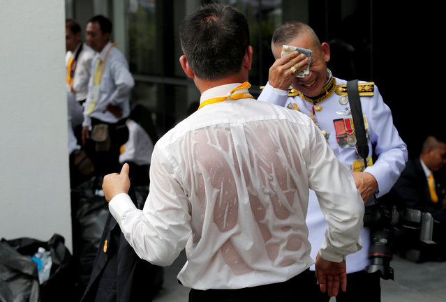 A journalist is seen soaked in sweat as he waits outside the balcony of Suddhaisavarya Prasad Hall at the Grand Palace, where of King Maha Vajiralongkorn will grant a public audience to receive the good wishes of the people in Bangkok, Thailand May 6, 2019. (Photo by Jorge Silva/Reuters)