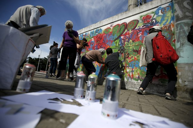 Participants spray on a wall during a graffiti class offered by the LATA 65 organization in Lisbon, Portugal May 14, 2015. (Photo by Rafael Marchante/Reuters)