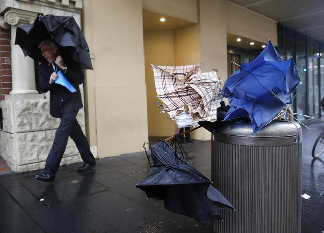 A man takes shelter next to discarded broken umbrellas in a litter bin during heavy rain in the Sydney central business district, Tuesday April 21, 2015 Sydney, Australia. (Photo by David Moir/AAP Image via AP Photo)
