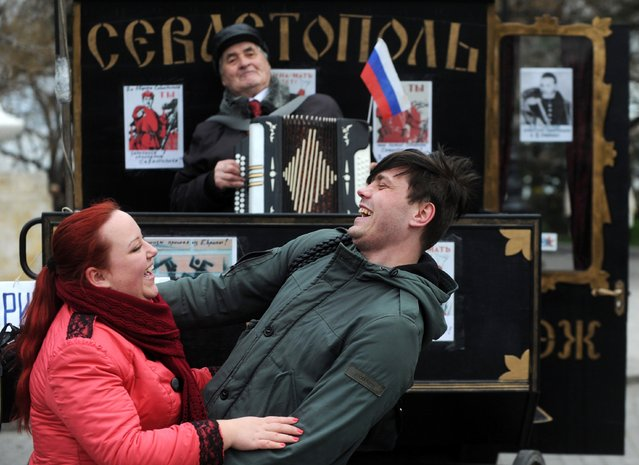 A man plays accordion as people dance during celebrations in Sevastopol on March 17, 2014. Crimea declared independence today and applied to join Russia while the Kremlin braced for sanctions after the flashpoint peninsula voted to leave Ukraine in a ballot that has fanned the worst East-West tensions since the Cold War. (Photo by Viktor Drachev/AFP Photo)