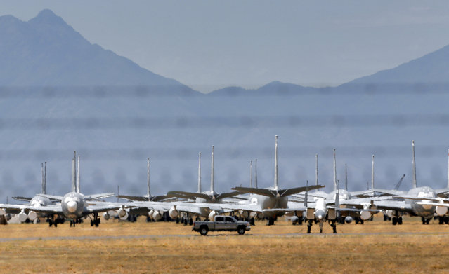Heat ripples rise off the desert floor as seen through a barb-wired fence as a pickup drives past stored military aircraft at the 309th Aerospace Maintenance and Regeneration Group boneyard, Thursday, May 21, 2015, in Tucson, Ariz. (Photo by Matt York/AP Photo)