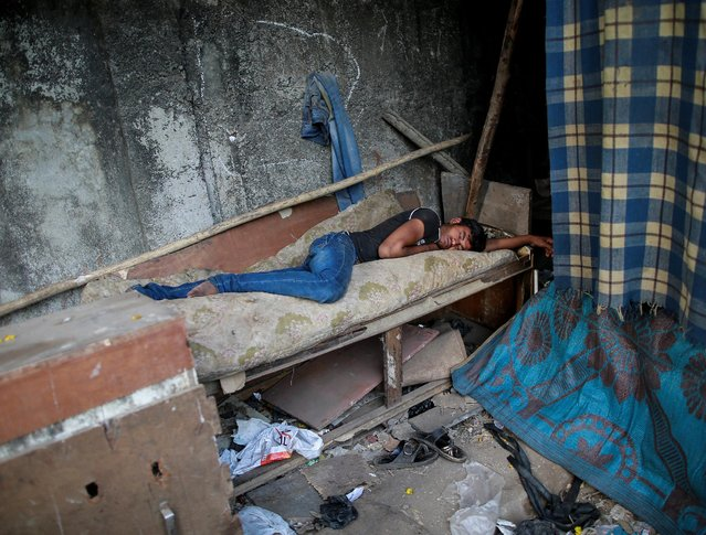 A man sleeps outside his shanty at a slum in Mumbai, India, April 13, 2016. (Photo by Danish Siddiqui/Reuters)