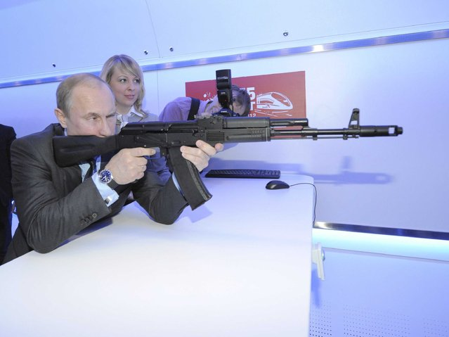 Vladimir Putin aims at a target with a replica of Kalashnikov assault rifle in Moscow, on April 26, 2012, while visiting a shooting gallery at an exhibition of Russian Railways' research center. (Photo by Alexei Druzhinin/AFP Photo/RIA Novosti)