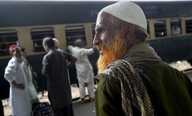 A man with a henna-dyed beard stands with others while waiting for a train to leave at  Cantonment Railways Station in Karachi, Pakistan, May 25, 2015. (Photo by Akhtar Soomro/Reuters)