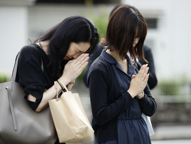 Women pray for the victims near the site of a knife attack in Kawasaki, near Tokyo Wednesday, May 29, 2019. A man carrying a knife in each hand attacked a group of schoolgirls waiting at a bus stop just outside Tokyo Tuesday. (Photo by Hiroki Yamauchi/Kyodo News via AP Photo)