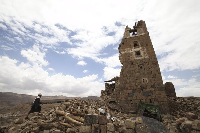 A man walks to a house that was damaged during an airstrike carried out by the Saudi-led coalition in Faj Attan village, Sanaa, Yemen May 7, 2015. (Photo by Mohamed al-Sayaghi/Reuters)