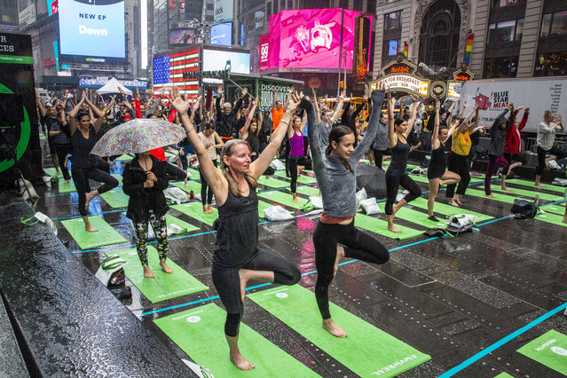 People participate in a mass yoga session celebrating Solstice in Times Square, Friday, June 21, 2019. (Photo by Natan Dvir)