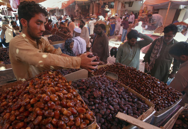 People buy dates, a favorite food for Muslims' fasting month of Ramadan, at a wholesale market in Karachi, Sunday, May 5, 2019. Muslims across the world will be observing Ramadan, when they refrain from eating, drinking and smoking from dawn to dusk. (Photo by Fareed Khan/AP Photo)