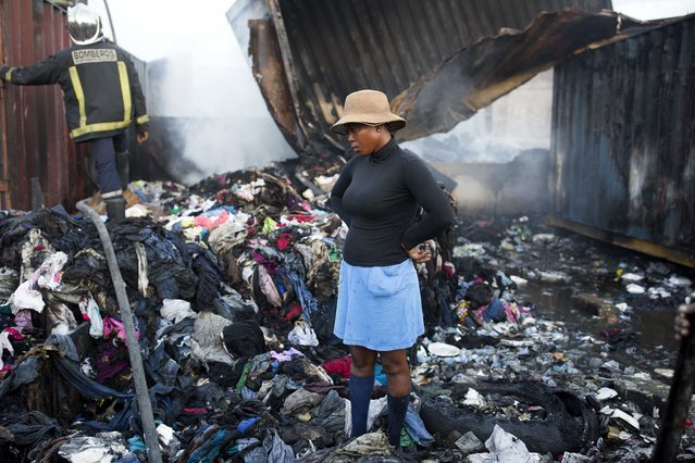 A woman stands in the middle of her fire damaged clothes after a massive fire at a market in Port-au-Prince, Haiti, Monday March 20, 2017. (Photo by Dieu Nalio Chery/AP Photo)