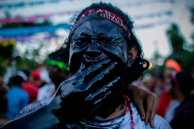 A catholic faithful smeared in burnt oil, takes part in the opening of the ten-day celebration of the Santo Domingo de Guzman festival in Managua, on August 1, 2019. The 10 days of festivities have their roots in the 1885 discovery of the 3-inch statue of Santo Domingo de Guzman  – who is also known as St. Dominic de Guzman, the founder of the Dominican religious order. In Central America the black devil, or El Cadejo, is an evil dog-like spirit with glowing red eyes that locals believe eats new born puppies. (Photo by Inti Ocon/AFP Photo)