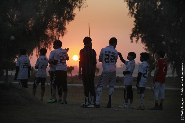 Children practice soccer at sunset in Baghdad, Iraq