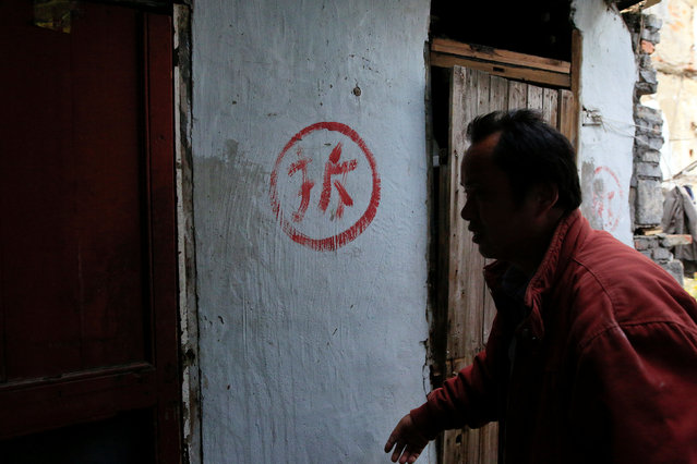 "A man surnamed Xu, 50, walks past a house carrying the Chinese character ""Chai"", meaning ""demolition"", in Guangfuli neighbourhood, in Shanghai, China, April 8, 2016. Xu's whole family used to live under the same roof together in Guangfuli. (Photo by Aly Song/Reuters)"