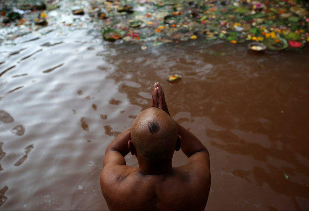 A devotee offers prayer as he takes a holy bath at Matathirtha to commemorate his departed mother during Mother's Day in Kathmandu, Nepal, May 6, 2016. (Photo by Navesh Chitrakar/Reuters)