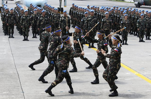"Armed Forces of the Philippines personnel deploying to the United Nations peacekeeping mission in Haiti, demonstrate their local martial arts ""Arnis De Mano"" skills during a sending-off ceremony at the Villamor air base in Pasay city, Metro Manila July 7, 2015. A new batch of more than a hundred soldiers are leaving on Wednesday for Haiti to take part in UN peacekeeping operations for a year, a military officer said. (Photo by Erik De Castro/Reuters)"