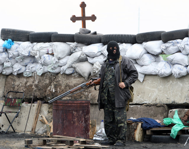 Armed men guard at the Kombikorm factory checkpoint, near Svyatogorsk town close to Slaviansk, Ukraine, 30 April 2014. Militants in Sloviansk are keeping dozens of hostages, including seven European military observers, who were detained in the city on 25 April while on a verification mission under the Organisation of Security and Cooperation in Europe (OSCE). (Photo by Igor Kovalenko/EPA)