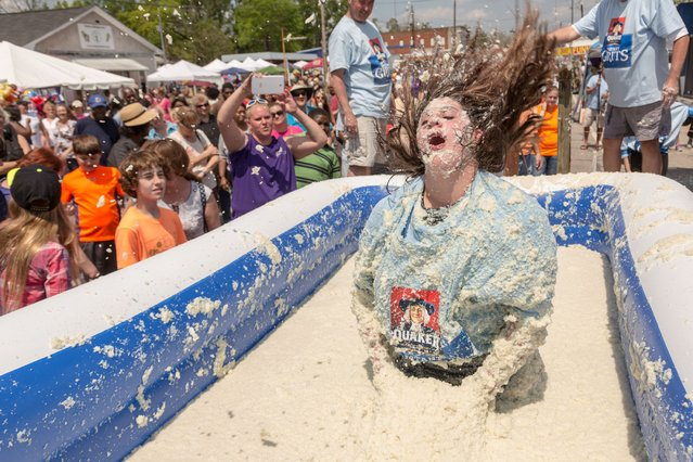 A young girl dives into a vat of grits during the Rolling in the Grits contest at the World Grits Festival in St George, South Carolina. (Photo by 2014 Richard Ellis)