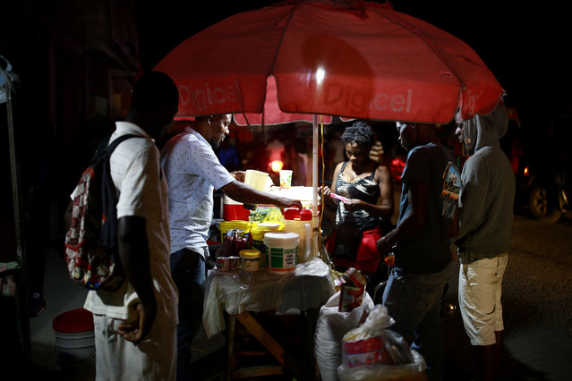 In this April 16, 2019 photo, street vendors sell juice in Petion-Ville, Haiti. The current fuel crisis is helping push Haiti's economy dangerously close to recession. (Photo by Dieu Nalio Chery/AP Photo)