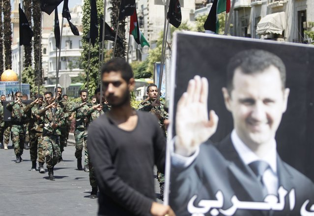 Palestinians living in Syria carry flags as one of them holds a picture depicting Syria's President Bashar al-Assad during a rally marking the annual al-Quds Day, or Jerusalem Day, on the last Friday of the Muslim holy month of Ramadan in Damascus, Syria July 10, 2015. (Photo by Omar Sanadiki/Reuters)