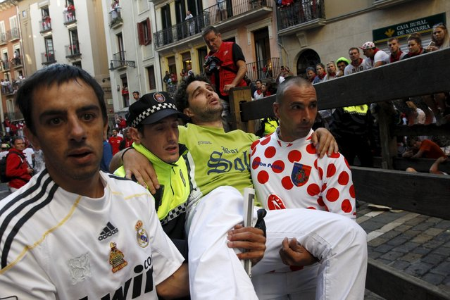 An injured unidentified runner is taken away following the seventh running of the bulls of the San Fermin festival in Pamplona, northern Spain, July 13, 2015. Two runners were gored in the run that lasted two minutes and twelve seconds, according to local media. (Photo by Joseba Etxaburu/Reuters)