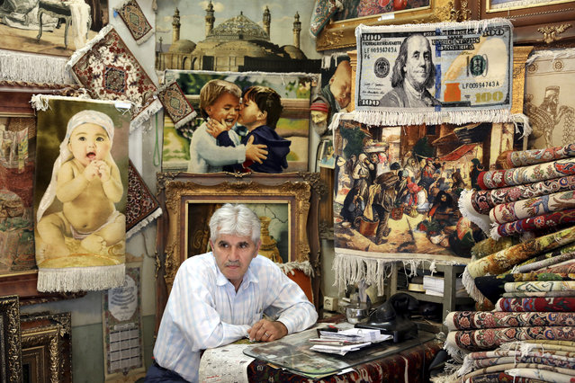 "A carpet merchant sits at his shop in the old main bazaar in Tehran, Iran, Tuesday, July 2, 2019. From an English-language teacher hoping for peace to an appliance salesman who applauded Donald Trump as a ""successful businessman"", all said they suffered from the economic hardships sparked by re-imposed and newly created American sanctions. (Photo by Ebrahim Noroozi/AP Photo)"