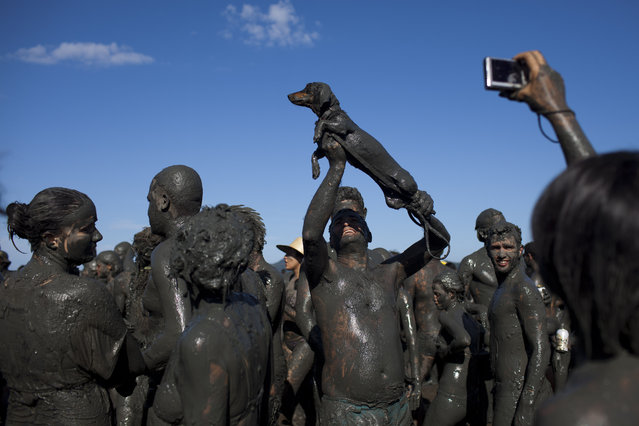 "A man covered in mud holds up his mud covered dog as another reveler takes a picture during the ""Bloco da Lama"" or ""Mud Block"" carnival parade in Parati, Brazil, Saturday Feb. 18, 2012. (Photo by Felipe Dana/AP Photo)"