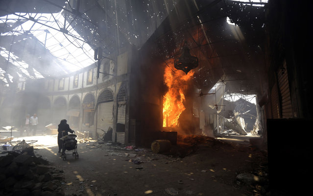A woman walks past a burning shop in the Maskuf market in the Old City of Homs, some 162 kilometres north of the capital Damascus, on May 12, 2014. (Photo by Joseph Eid/AFP Photo)