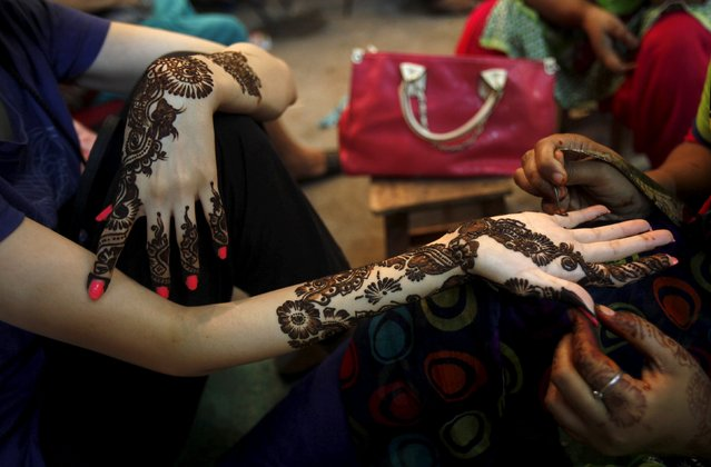 A girl gets her hands decorated with traditional henna patterns at a roadside stall ahead of Eid-al Fitr to mark the end of the holy fasting month of Ramadan in Karachi, Pakistan, July 17, 2015. (Photo by Akhtar Soomro/Reuters)