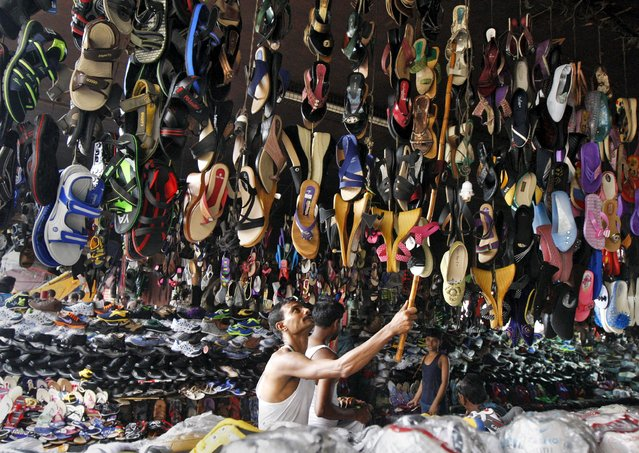 A vendor hangs footwear for sale at a stall under a flyover at a market in Kolkata, India, July 13, 2015. (Photo by Rupak De Chowdhuri/Reuters)