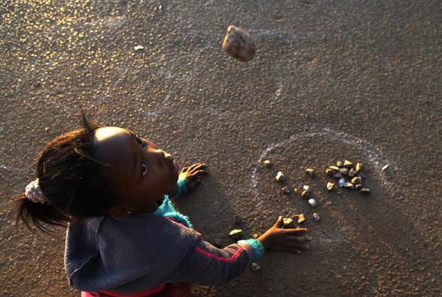"""In this Wednesday, July 8, 2015 photo, Ellen Rathobotha, plays a indigenous game called """"Diketo"""" in in Kagiso, west of Johannesburg, South Africa. In the game, which requires good hand-eye coordination, stones are placed in a circle or a square and each player then tries to grab the most stones, throw them in the air and catch them in one hand until all the stones are back in the circle or square. (Photo by Themba Hadebe/AP Photo)"""