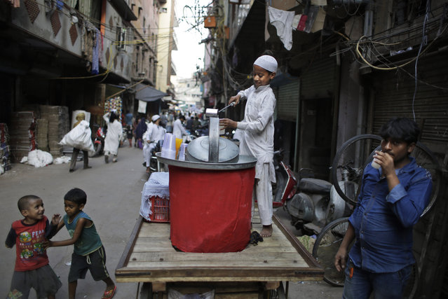 A Indian Muslim boy serves lemon water to passerby's in an alleyway on a hot afternoon in New Delhi, India, Friday, May 13, 2016. Much of India is reeling under a heat wave and severe drought conditions that have decimated crops, killed livestock and left many Indians without enough water for their daily needs. Rivers, lakes and dams have dried up in parts of the western states of Maharashtra and Gujarat. (Photo by Altaf Qadri/AP Photo)