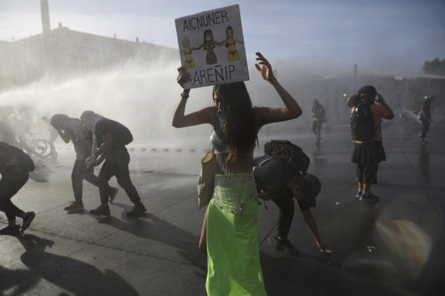Demonstrators are sprayed by a police water cannon during an anti-government protest in Santiago, Chile, Thursday, October 31, 2019. Chile has been facing days of unrest, triggered by a relatively minor increase in subway fares. The protests have shaken a nation noted for economic stability over the past decades, which has seen steadily declining poverty despite persistent high rates of inequality. (Photo by Rodrigo Abd/AP Photo)