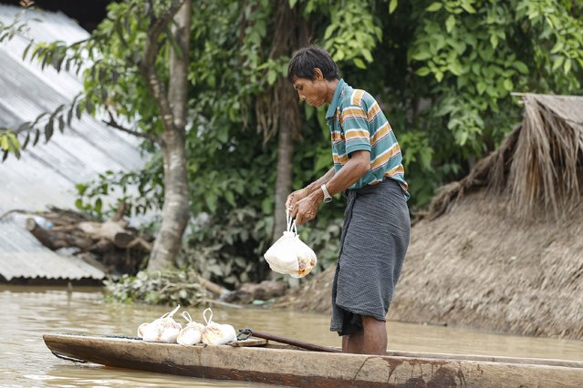 A man holds food collected from local donors at a village in Kawlin township, Sagaing division, Myanmar, July 21, 2015. (Photo by Soe Zeya Tun/Reuters)