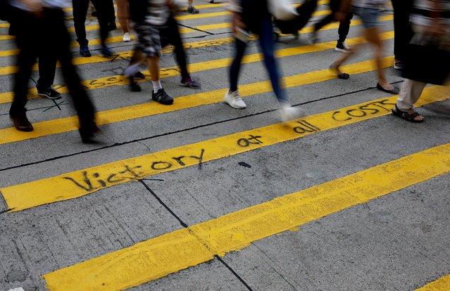 Pedestrians walk over graffiti on a crossing in Hong Kong, China, November 4, 2019. (Photo by Kim Kyung-Hoon/Reuters)