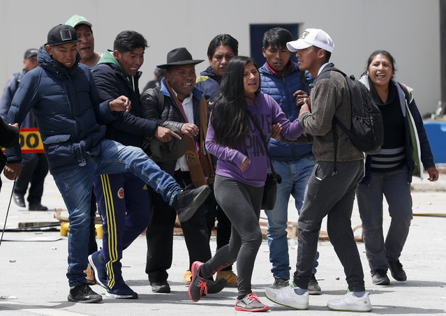One person that is part of a group of followers of President Evo Morales kicks towards a couple in La Paz, Bolivia, Sunday, November 10, 2019. President Evo Morales is calling for new presidential elections and an overhaul of the electoral system Sunday after a preliminary report by the Organization of American States found irregularities in the Oct. 20 elections. (Photo by Juan Karita/AP Photo)