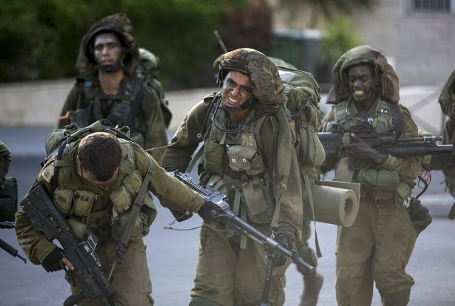 An Israeli soldier (C) from the Nahal Brigade is helped by a comrade during a march at the end of combat training in Jerusalem July 23, 2015. (Photo by Baz Ratner/Reuters)