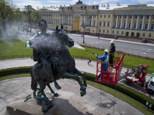 A worker washes a city landmarks, the equestrian statue of Peter the Great known as the Bronze Horseman by French sculptor Etienne Maurice Falconet, in St.Petersburg, Russia, Friday, May 26, 2017. (Photo by Dmitri Lovetsky/AP Photo)