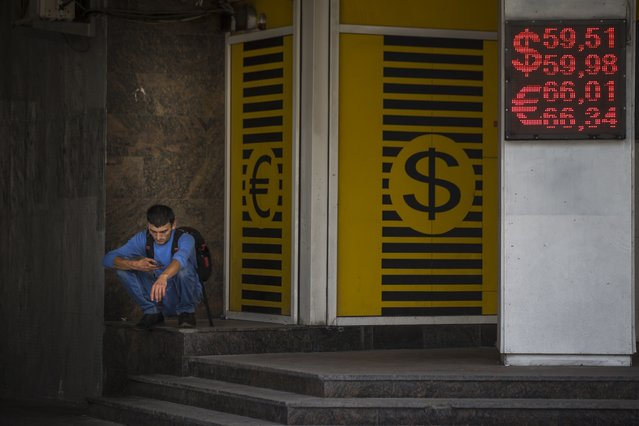 A man looks at his cell phone next to an exchange office sign showing currency exchange rate in Moscow, Russia, Monday, July 27, 2015. The Russian ruble dropped by 2 percent on Monday, to nearly 60 rubles against the dollar, battered by low oil prices. (Photo by Alexander Zemlianichenko/AP Photo)