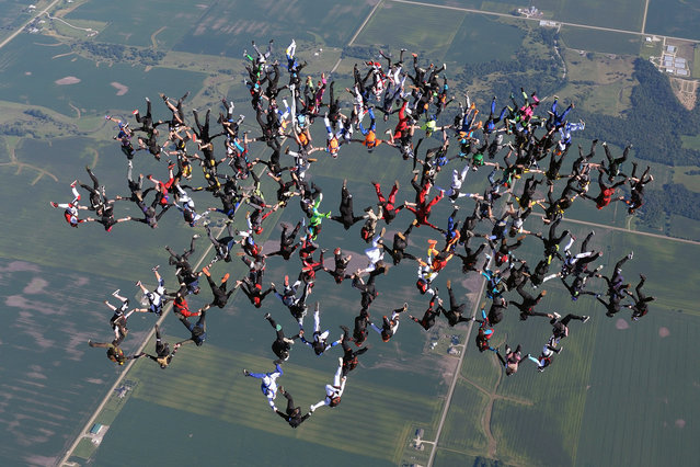 In this photo provided by Gustavo Cabana, members of an international team of skydivers join hands, flying head-down to build their world record skydiving formation, Friday, July 31, 2015, over Ottawa, Ill. (Photo by Jason Peters via AP Photo)