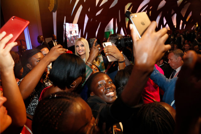 People crowd around U.S. White House senior adviser Ivanka Trump, back left, to take selfies with her at the end of the Women Entrepreneurs Finance Initative, or We-Fi, event sponsored by the World Bank Group, Wednesday, April 17, 2019, in Abidjan, Ivory Coast. Ivanka Trump is promoting a White House global economic program for women. (Photo by Jacquelyn Martin/AP Photo)