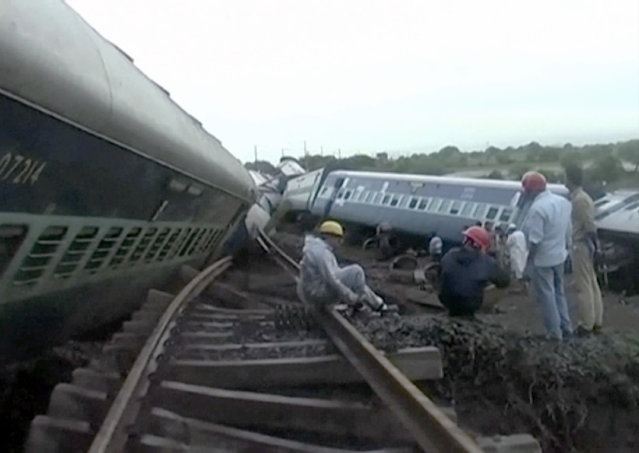 In this image made from video, people gather by the twisted track alongside two derailed trains in Harda in Madhya Pradesh state, India, Wednesday, August 5, 2015. (Photo via AP Video)