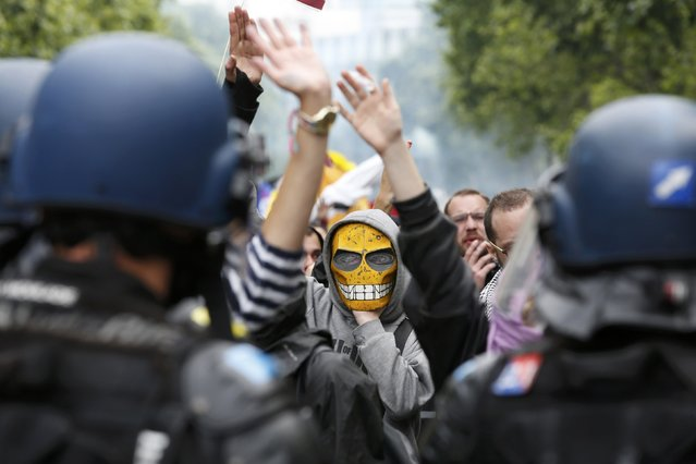 A masked youth reacts in front of French gendarmes during a demonstration in Paris as part of nationwide protests against plans to reform French labour laws, France, June 14, 2016. (Photo by Philippe Wojazer/Reuters)