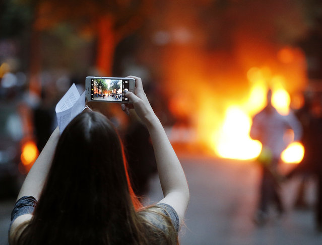A young woman takes a picture of a burning barricade during a protest against the G-20 summit in Hamburg, northern Germany, Friday, July 7, 2017. The leaders of the group of 20 meet July 7 and 8. (Photo by Michael Probst/AP Photo)