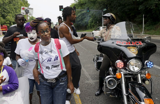 A St. Louis County motorcycle police officer clasps hands with a protester at a protest march in Ferguson, Missouri August 8, 2015. (Photo by Rick Wilking/Reuters)