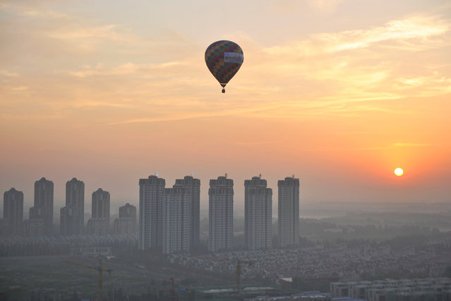 A hot air balloon flies over residential buildings in Wuqing District of Tianjin, China July 11, 2017. (Photo by Reuters/China Stringer Network)