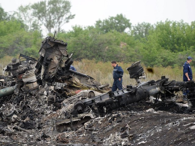 Rescuers stand on the site of the crash of a Malaysian airliner near the town of Shaktarsk, in rebel-held east Ukraine. (Photo by Dominique Faget/AFP Photo)